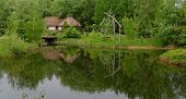 Traditional farmer's house reflecting in a pond in open air museum Kiev Ukraine
