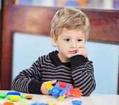 Thoughtful little boy with blocks looking away in preschool