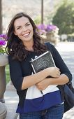 Portrait  of Pretty Young Female Student Carrying Books on School Campus.