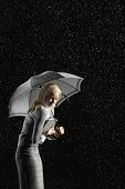 Side view of a businesswoman hunching under umbrella for protection from rain