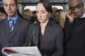 image of commutator  - Group of multiethnic commuters in a train with woman reading newspaper - JPG