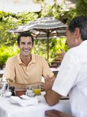 Two happy men conversing at an outdoor caf�?�?�?�©