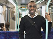 Portrait of a smiling African American commuter standing in train