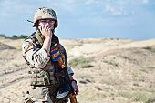 stock photo of kalashnikov  - iraqi soldier in the desert talking portable radio station - JPG