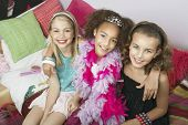 stock photo of tweenie  - Portrait of three multiethnic girls sitting with arms around on trendy sofa at a slumber party - JPG