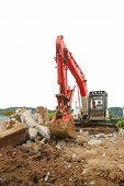 image of track-hoe  - Large excavator or track hoe and a concrete refuge pile working on new tennis center Stewart Park Roseburg OR - JPG