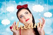 stock photo of daydreaming  - Attractive young pinup girl looking up to the clouds of inspiration with the words dream in hand - JPG