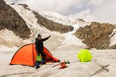 The Climber Standing Near Tent On Glacier