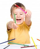 Little boy is playing with color pencils throwing them on a table, isolated over white
