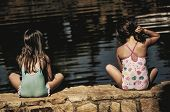 Girls sitting by a pond