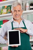 Portrait of happy senior male owner showing digital tablet in grocery store