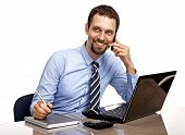 Successful businessman talking by cellphone while working with laptop isolated on white