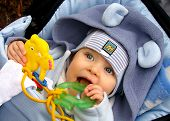 foto of teething baby  - A baby lying and teething a green toy outdoor - JPG