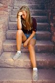 Thoughtful Girl With Blue Eyes Sitting At Stone Brick Stairs