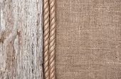 stock photo of rude  - Burlap background bordered by rope and rude old wood - JPG