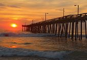 stock photo of outer  - The rising sun peeks through clouds and is reflected in waves by the Nags Head fishing pier on the outer banks of North Carolina