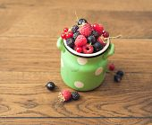 Pottery jar with berries on a wooden background.