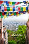picture of nepali  - Tibetan prayer flags between buildings and view to Kathmandu from Swayambhunath stupa in Nepal - JPG
