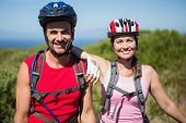 Active couple cycling in the countryside smiling at camera on a sunny day