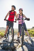 Fit cyclist couple looking ahead on mountain trail on a sunny day