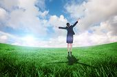 Excited businesswoman cheering against green field under blue sky