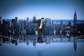 Mature businessman doing a balancing act on tightrope against mirror image of city skyline