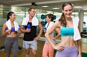 Fit woman smiling at camera in busy fitness studio at the gym