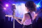 Pretty girl playing guitar against digitally generated disco ball background