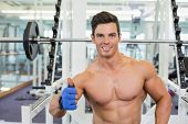 Portrait of a smiling shirtless muscular man giving thumbs up in gym