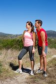 Active couple standing on country terrain on a sunny day