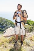 Handsome hiker holding binoculars on mountain trail on a sunny day