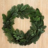 Christmas and winter spruce fir green wreath over oak background.
