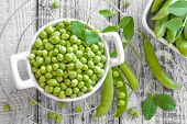 pic of peas  - Raw green peas and in a podson a table - JPG