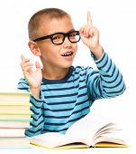 Cute little boy is reading a book while wearing glasses and explaining something gesturing with hand