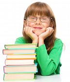 Cute little girl is reading a book while wearing glasses supporting his head with hands, isolated over white