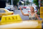 Business Woman Stopping Yellow Taxi