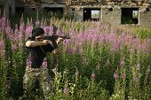 picture of terrorist  - Man with gun among flowers. Russian terrorist.