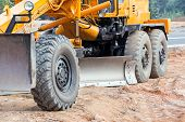 stock photo of movers  - Large yellow road grader working on road construction - JPG