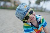 Cute boy in denim hat and sunglasses