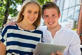 Outdoor portrait of one young couple using a digital tablet