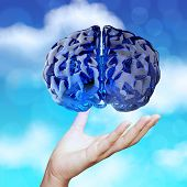 Medical Doctor Hand Showing 3D Blue Glass Human Brain On Nature Background As Concept
