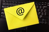 E-mail concept yellow letter on laptop keyboard with an at symbol