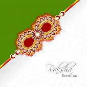 Beautiful golden rakhi on green and floral decorated grey background for Raksha Bandhan celebrations
