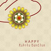 Beautiful rakhi on seamless floral decorated brown background for the festival of Raksha Bandhan.