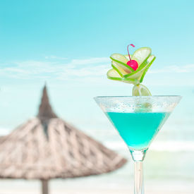 pic of cocktail menu  - Blue margarita cocktail with lime fruit and cherry decoration at tropical ocean beach with umbrella - JPG