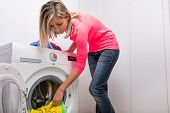 Housework: young woman doing laundry - putting colorful garments into the washing machine (shallow DOF; color toned image)
