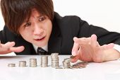 picture of collapse  - stack of coins collapsed when businessman put a coin - JPG