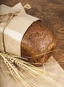 Black Bread In A Paper Packing With Ears Of Wheat