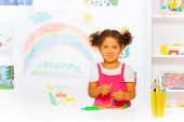 Little girl play with modeling clay in classroom
