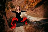 image of levitation  - Young woman in black dress levitating in the forest - JPG